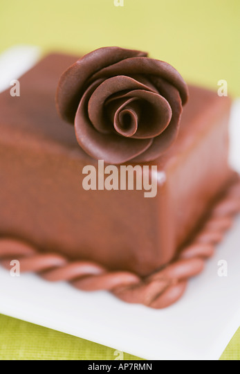 A chocolate rose on a cake - Stock Image