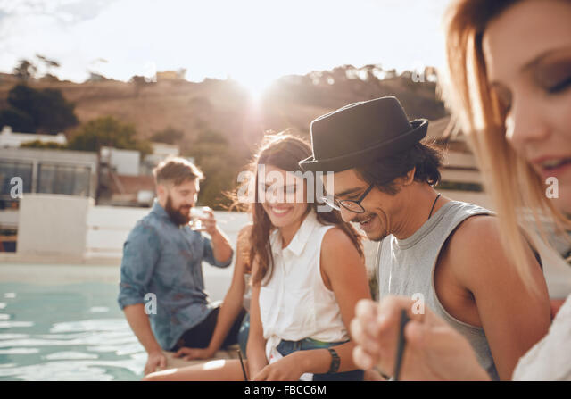 Outdoor shot of happy young man sitting by the pool with his friends partying. Group of young people hanging around - Stock Image