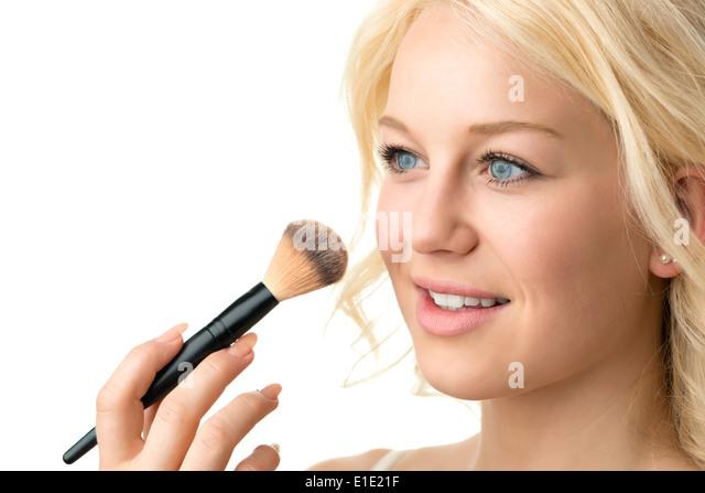 Closeup makeup applying of a blond woman - Stock Image