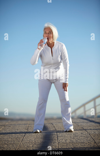 Mature woman drinking water on walk - Stock Image