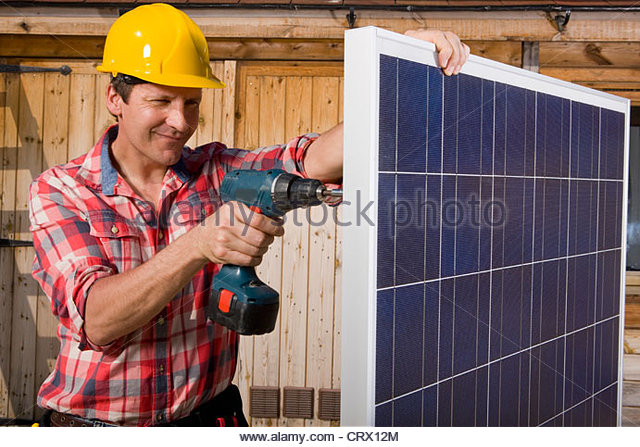 Engineer drilling into solar panel - Stock Image