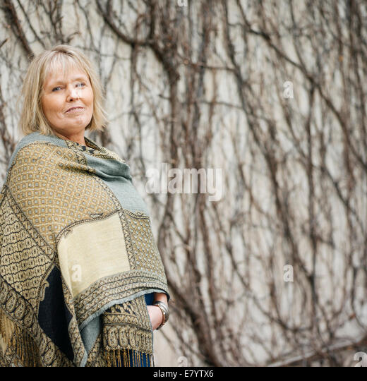 Senior woman in shawl standing against wall covered in leafless ivy - Stock Image