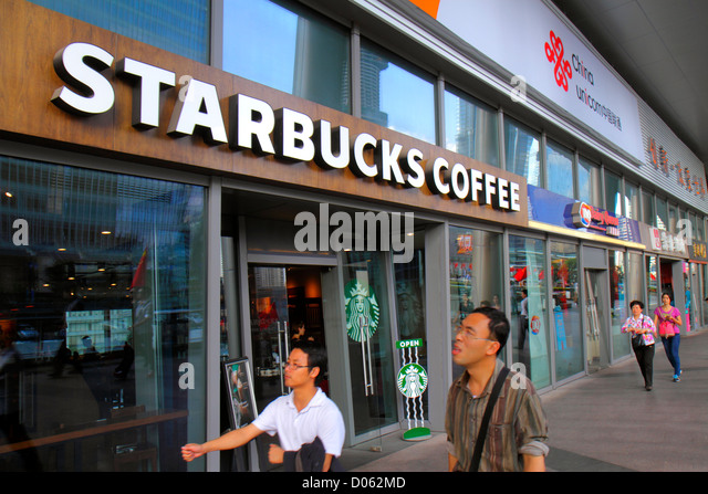 Shanghai China Pudong Lujiazui Financial District Lujiazui East Road Starbucks Coffee front entrance Asian man - Stock Image
