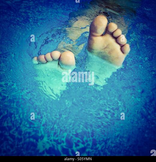 Bare feet on a pool - Stock Image