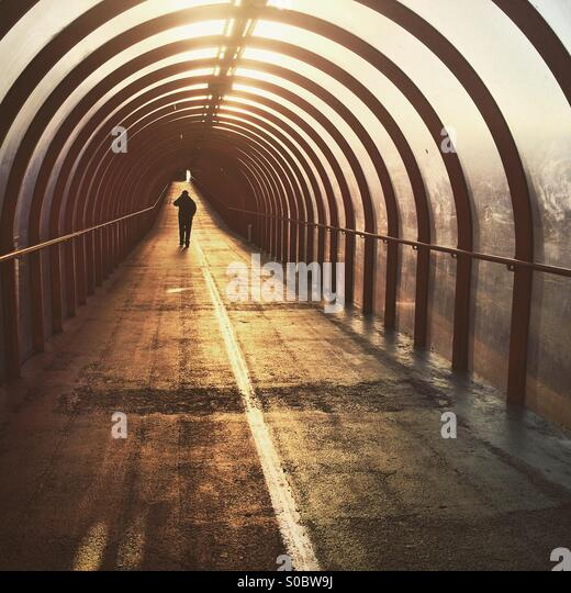 A silhouette of a man walking down a tunnel at sunrise in Glasgow - Stock Image