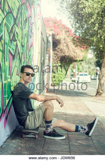 Portrait of young man sitting on skateboard, leaning against graffitied wall - Stock-Bilder