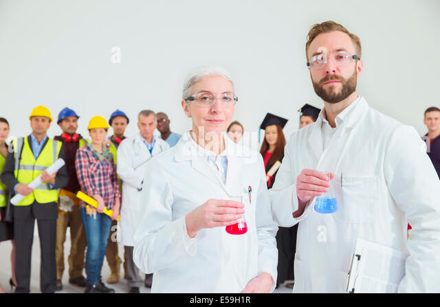 Portrait of scientists with workforce in background - Stock Image