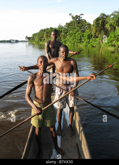 Three Lingala fishermen standing up to paddle large dugout canoe on Congo River Democratic Republic of Congo - Stock-Bilder