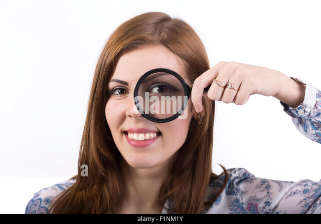Female face looking through magnifier - Stock Image