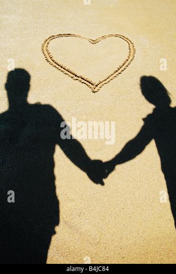 couple holding hands on the beach - Stock-Bilder