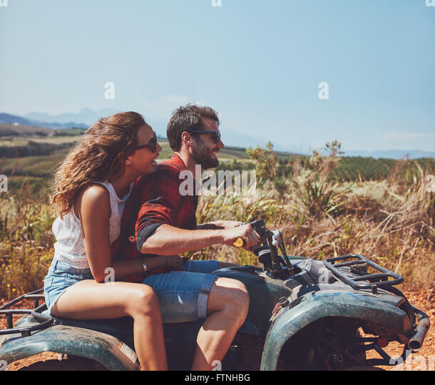 Side view of young man and woman riding on a quad bike on a summer holiday. Couple enjoying holidays on a quad bike - Stock-Bilder