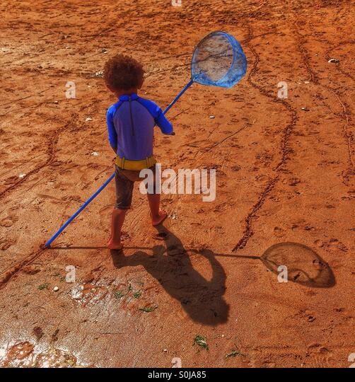 A little boys shadow in the sand. - Stock Image