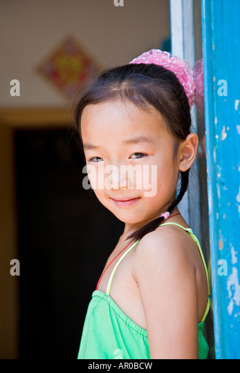 Young asian oriental peasant Chinese girl in green dress facing left looking over shoulder to camera China JMH3022 - Stock Image