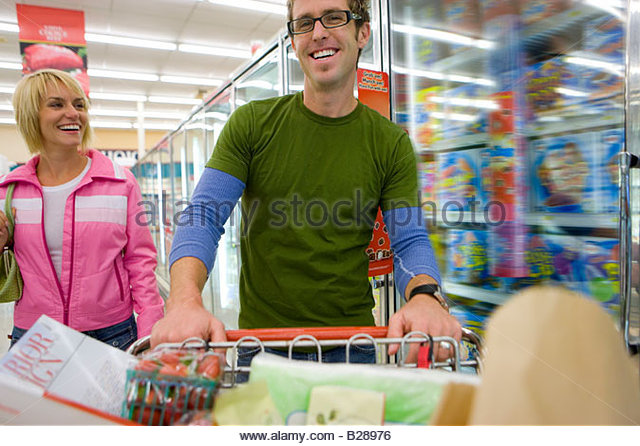 Couple grocery shopping in frozen foods section - Stock Image