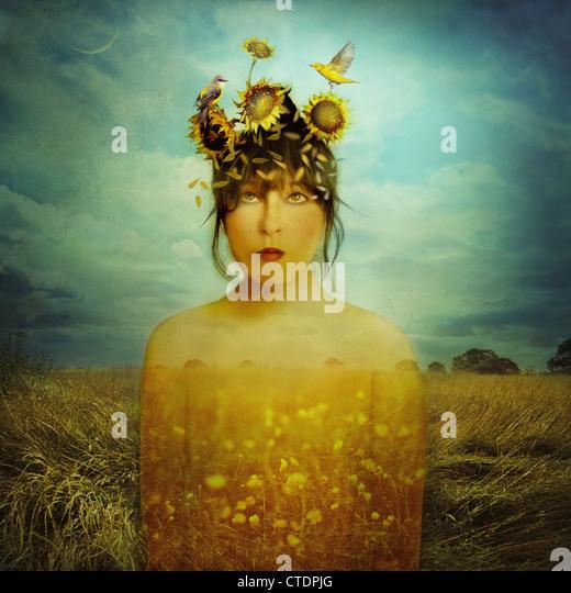 Field Dreamer,woman in field wearing sunflower wreath with birds - Stock Image