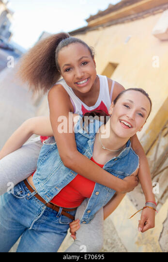 Teenage girl giving friend piggyback ride - Stock Image