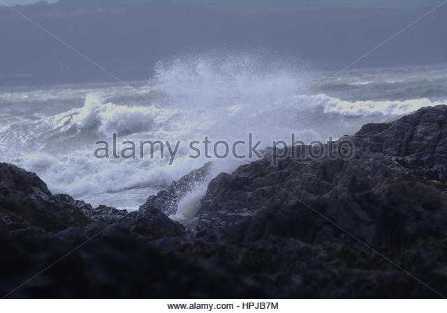 Coastal waves crashing into rocks during a storm - Stock Image