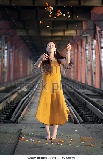 India, Uttar Pradesh, Varanasi, Young woman throwing petals - Stock-Bilder