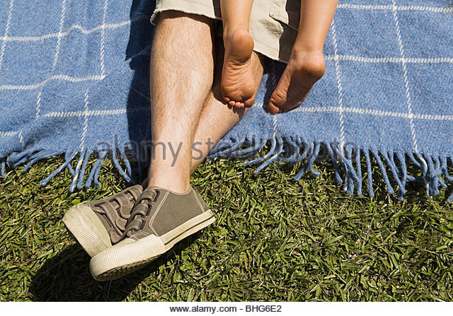 Low section view of man and boy relaxing on picnic blanket - Stock Image