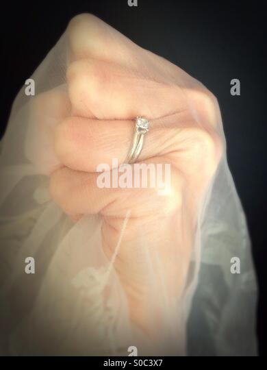 A tight fist wearing a wedding ring, and gripping sheer gauzy fabric. - Stock Image
