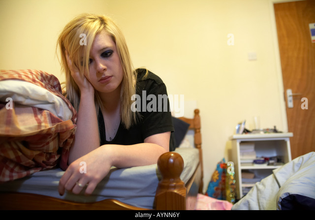 young teenage woman crying lying on bed in messy bedsit bedroom holding her head in one hand - Stock-Bilder