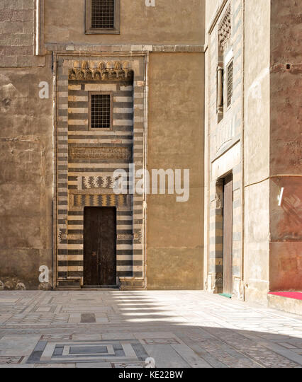 Wooden aged door surrounded by striped black and white marble decorations and stone wallat the courtyard of Sultan - Stock Image