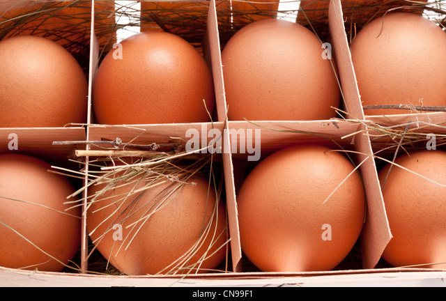 Eggs with a straw in a wooden basket - Stock Image