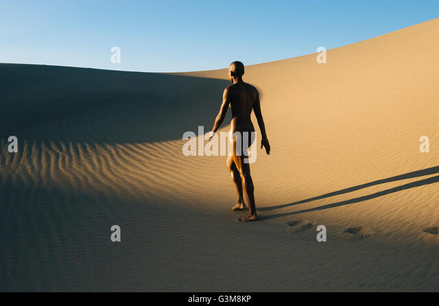 Nude woman walking in desert - Stock Image