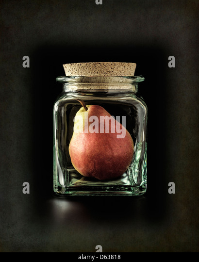 Pear in glass bottle - Stock Image