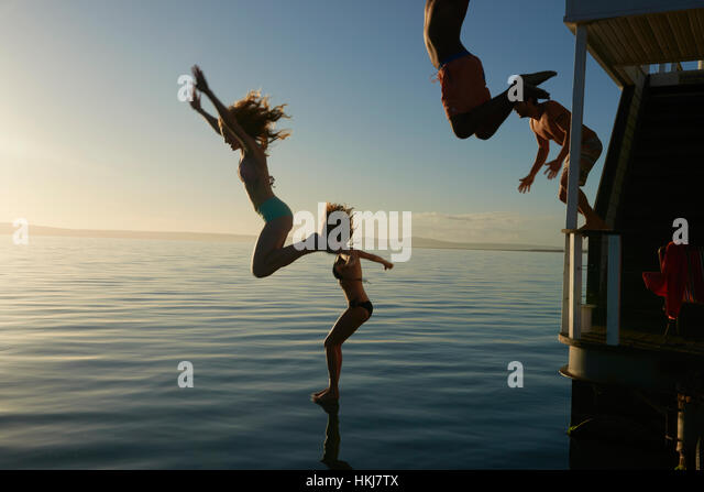 Young adult friends jumping from summer houseboat into sunset ocean - Stock-Bilder