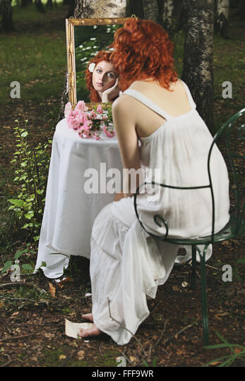 Red hair woman mirror reflection in a forest. Surreal and vintage - Stock-Bilder