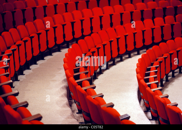 Curved rows of red seats in an auditorium. - Stock-Bilder