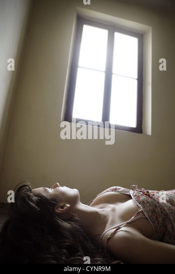 a girl lying on the floor looking at a bright window - Stock Image