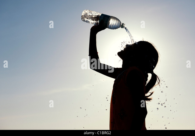 Indian girl cooling off with bottled water. Silhouette - Stock Image