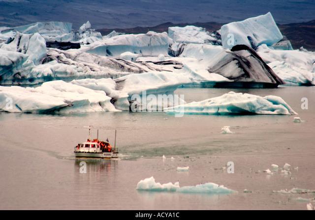 Iceland Jokulsarlon Glacial Lagoon Icebergs melting sunset near activ vulcano Vatnajoekull tourist boat - Stock Image