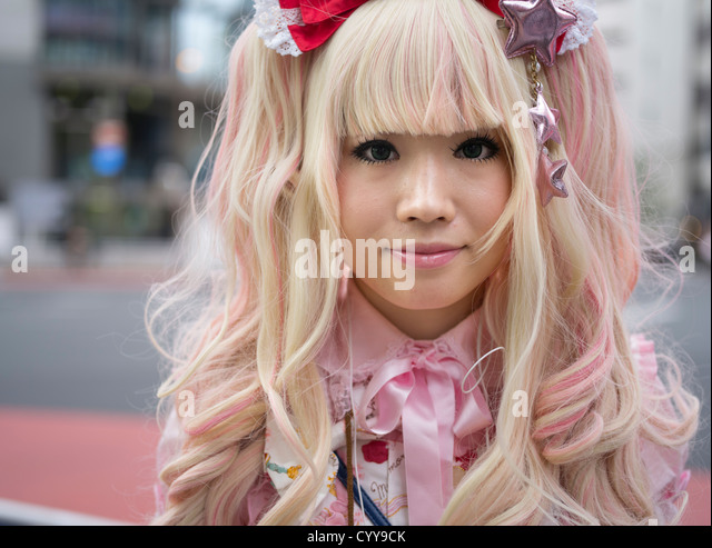 Young Japanese woman in kawaii lolita alternative fashion costume with blonde hair and pink dress - Stock-Bilder