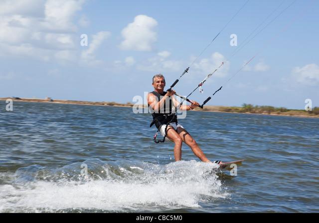 Older man wind surfing on lake - Stock Image