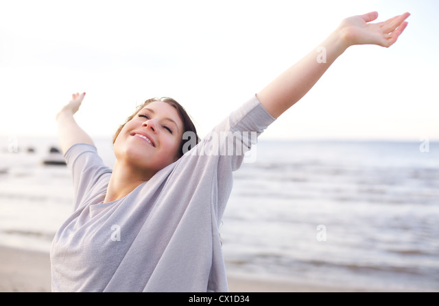 Woman stretching her arms to enjoy the fresh air of the sea - Stock Image