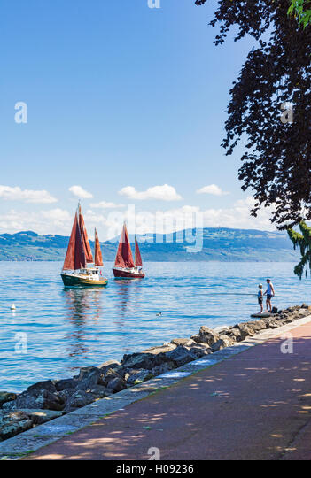 Couple fishing off the promenade of Evian as traditional sailing boats go by on Lake Geneva, Évian-les-Bains, - Stock Image