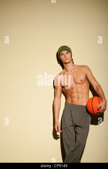 Portrait of Healthy and good looking young caucasian man in long pants holding a basketball. - Stock Image