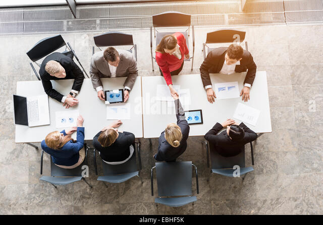 Overhead view of business team shaking hands with client at desk in office - Stock Image