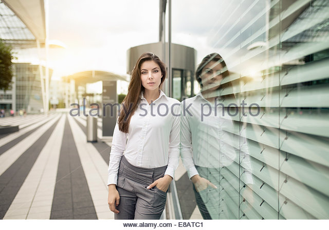 Businesswoman leaning against window, portrait - Stock-Bilder