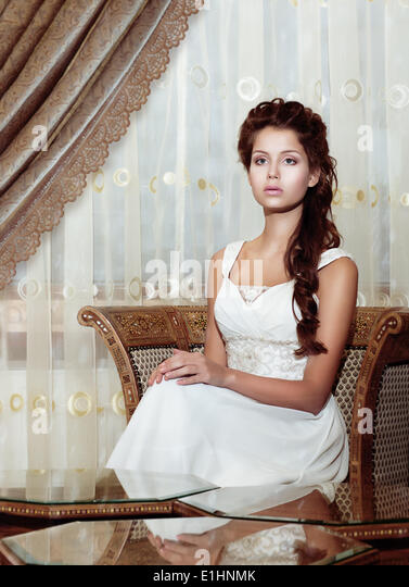 Femininity. Brown Hair Woman Bride in Wedding Dress sitting. Classic Romantic Interior - Stock Image