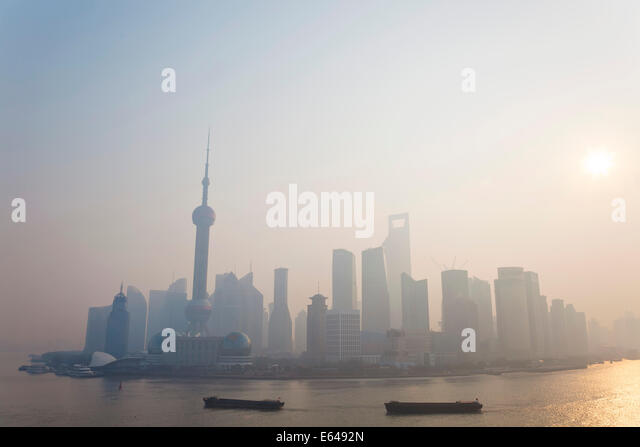Sunrise over Pudong skyline & barges on Huangpu River, Shanghai, China - Stock Image