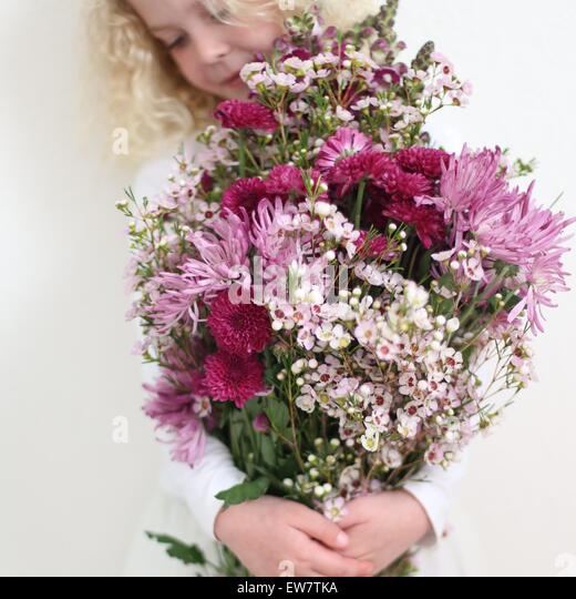Girl holding large bunch of pink flowers - Stock Image