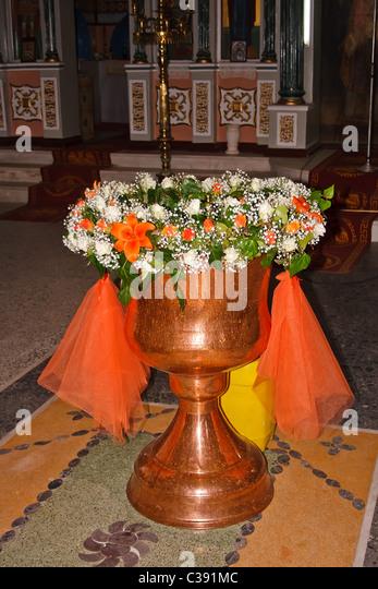 Greek-Orthodox flower decorated baptismal font - Stock-Bilder