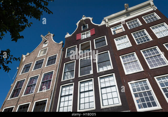 Classic canal-side buildings with hooks for lifting goods in Amsterdam - Stock Image