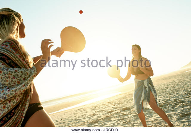 Two smiling young female friends in bikinis laughing and playing paddle ball together on a sandy beach on a sunny - Stock Image