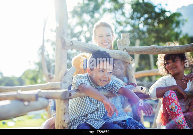 Teacher and students playing on play structure - Stock-Bilder