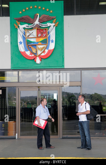 Panama City Panama Aeropuerto Tocumen airport PTY aviation terminal entrance door national shield man standing - Stock Image